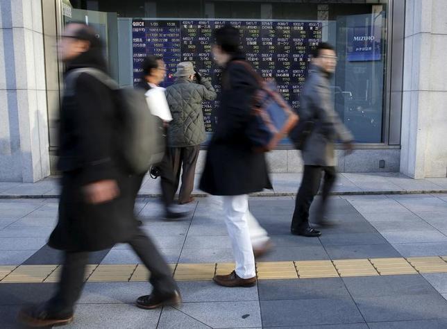 2月21日、寄り付きの東京株式市場で、日経平均は前営業日比16円79銭高の1万9267円87銭となり、小幅続伸して始まった。写真は株価ボードを眺める人々、都内で昨年1月撮影(2017年 ロイター/Toru Hanai)