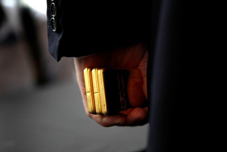 FILE PHOTO: Donald Trump holds three bars of gold bullion in New York, U.S., September 15, 2011.   REUTERS/Mike Segar/File Photo