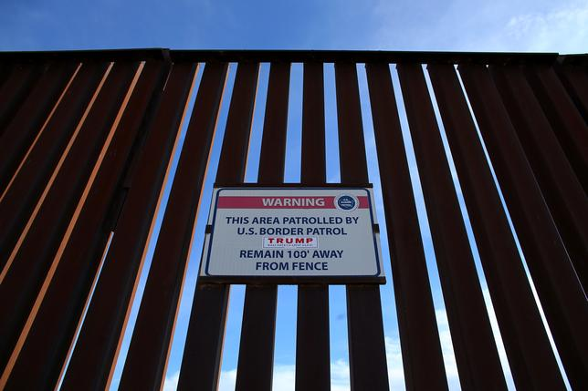A Donald Trump for President campaign sticker is shown attached to a U.S. Customs sign hanging on the border fence between Mexico and the United States near Calexico, California, U.S. February 8, 2017. REUTERS/Mike Blake