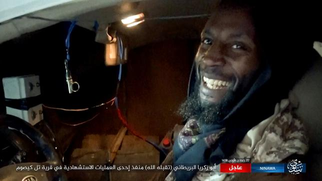 Still image shows British militant Abu-Zakariya al-Britani smiling and seated inside a car with wires hanging off him at an unknown location, in this undated video taken from social media. Social media website/via Reuters
