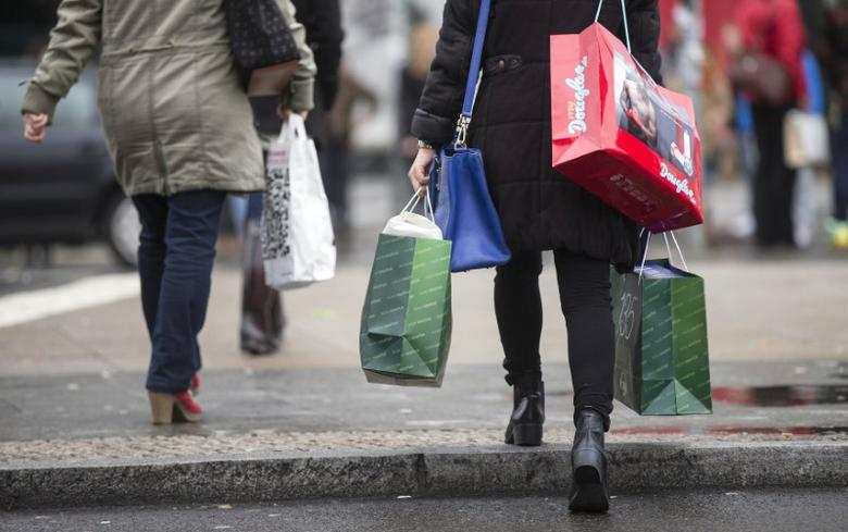People carry bags outside a shopping mall on the last day of Christmas shopping in Berlin December 23, 2014. REUTERS/Hannibal Hanschke