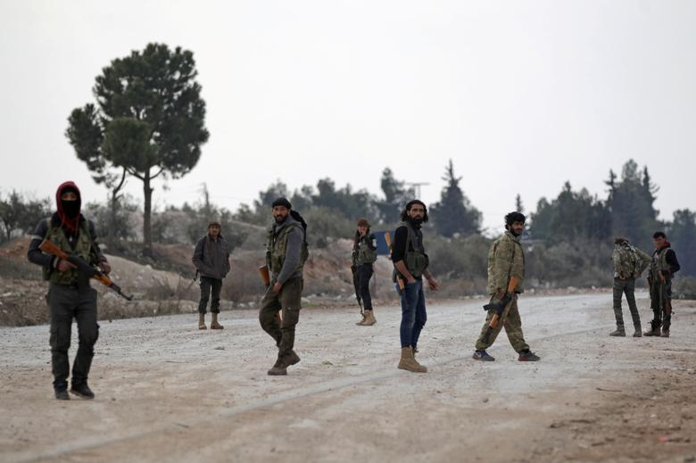 FILE PHOTO - Free Syrian Army fighters carry their weapons as they stand on the outskirts of the northern Syrian town of al-Bab, Syria February 4, 2017. Picture taken February 4, 2017. REUTERS/Khalil Ashawi /File photo