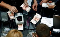 A shop assistant (L) counts Russian rouble banknotes as customers gather at a store selling Apple products during the launch of the new iPhone 7 sales at the State Department Store, GUM, in central Moscow, Russia September 23, 2016. REUTERS/Sergei Karpukhin - RTSP33Z
