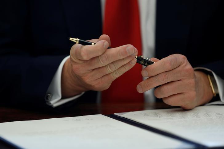 U.S. President Donald Trump prepares to sign an executive order on regulatory reform at his desk in the Oval Office at the White House, U.S. February 24, 2017. REUTERS/Jonathan Ernst