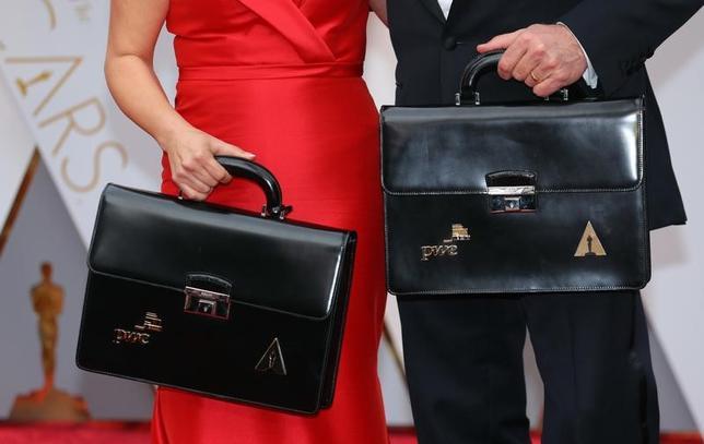 2月27日、米WSJ紙と芸能サイト「TMZ.com」は、アカデミー授賞式で封印された封筒を渡す責任者の1人である、プライス・ウォーターハウス・クーパー(PwC)の会計士ブライアン・カリナン氏が、主演女優賞を獲得したエマ・ストーンの舞台裏の写真を、このハプニングが起こる数分前にツイッターに投稿していたと報じた。写真は26日撮影、封筒の入ったブリーフケースを持つカリナン氏(右)とマーサ・ルイズ氏(左)(2017年 ロイター/Mike Blake )