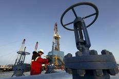Рабочий на Имилорском месторождении Лукойла под Когалымом 25 января 2016 года. Россия в феврале 2017 года снизила добычу нефти до 1,515 миллиона тонн в сутки или около 11,1 миллиона баррелей в сутки, сказали Рейтер источники, знакомые со статистикой.     REUTERS/Sergei Karpukhin/File Photo