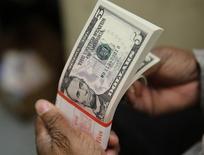 Una persona contando billetes de cinco dólares en la Casa de la Moneda en Washington, mar 26, 2015. El dólar alcanzó un máximo de siete semanas el miércoles, luego de que unos comentarios de dos importantes funcionarios de la Reserva Federal aumentaron las expectativas de que el banco central estadounidense está más cerca de subir nuevamente las tasas de interés.  REUTERS/Gary Cameron/File Photo