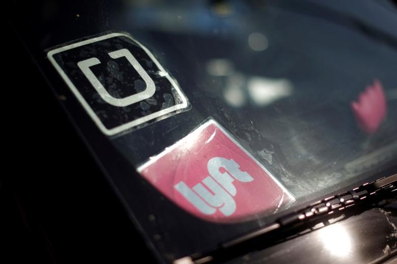 A driver displays Uber and Lyft ride sharing signs in his car windscreen in Santa Monica, California, U.S., May 23, 2016.  REUTERS/Lucy Nicholson/Files