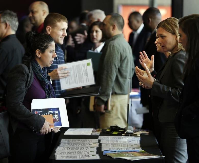 Legal firm Hogan Lovells representative Nina LeClair (2nd R) talks to U.S. military veteran applicants (L) at a hiring fair for veteran job seekers and military spouses at the Verizon Center in Washington April 9, 2014.   REUTERS/Gary Cameron