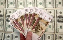 Долларовые и рублевые купюры в Сараево 9 марта 2015 года. Рубль подешевел в четверг, ускорив вечером негативную динамику вместе с валютами-аналогами против повсеместно дорожающего доллара США в ожидании повышения ставки ФРС, одновременно реагируя и на сильное внутридневное падение нефти. REUTERS/Dado Ruvic