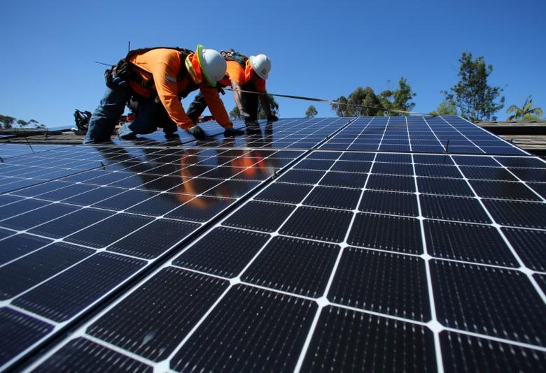 Solar installers place solar panels on the roof of a residential home in Scripps Ranch, San Diego, California, U.S. October 14, 2016. REUTERS/Mike Blake