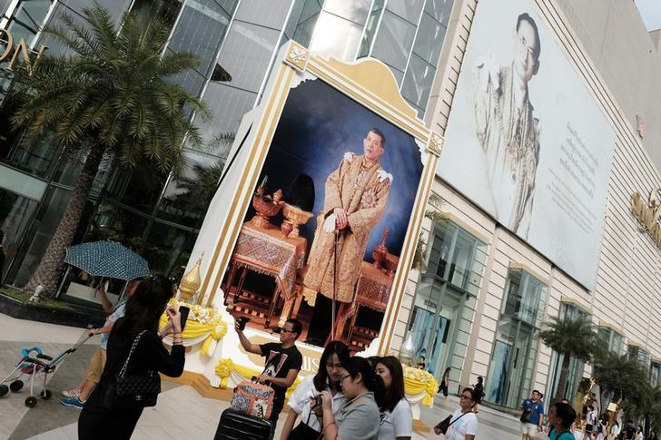 People walk past a portrait of Thailand's King Maha Vajiralongkorn Bodindradebayavarangkun and the late King Bhumibol Adulyadej at a department store in central Bangkok, Thailand, January 17, 2017. REUTERS/Athit Perawongmetha/Files