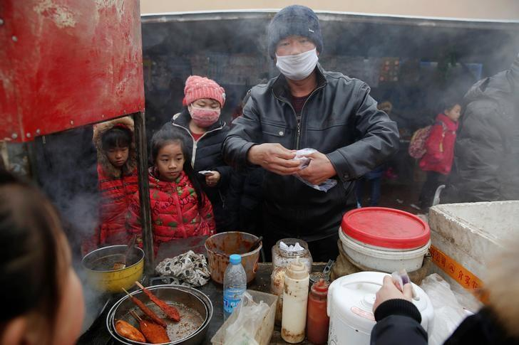Children buy food outside their school as heavy smog blankets Shenfang in Hebei province, on an very polluted day December 20, 2016.   REUTERS/Damir Sagolj/File Photo