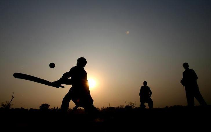 Children play cricket near the Wagah border crossing with India, near Lahore, in Pakistan, where the English cricket team paid a visit, 6 December 2005. REUTERS/ Jason O'Brien/File Photo
