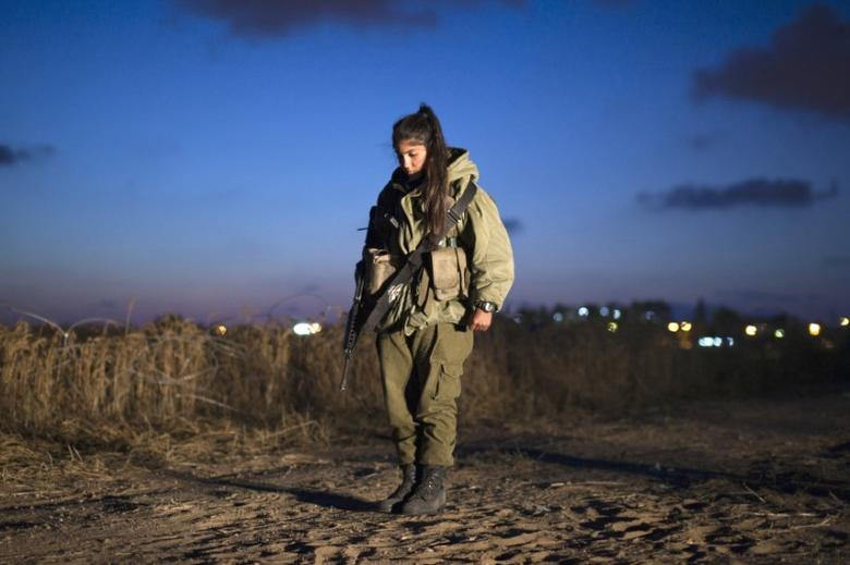 An Israeli soldier stands still at an Iron Dome unit in the coastal city of Ashkelon, north of the Gaza Strip, as a one-minute siren marking Memorial Day is sounded across Israel May 8, 2011.  REUTERS/Amir Cohen/Files