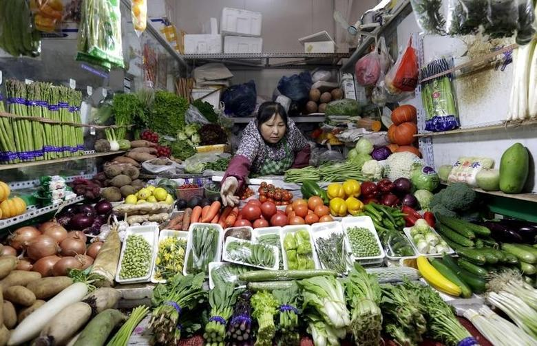 A vendor reaches out for vegetables at her shop in a market in Beijing, February 18, 2016. REUTERS/Jason Lee/Files