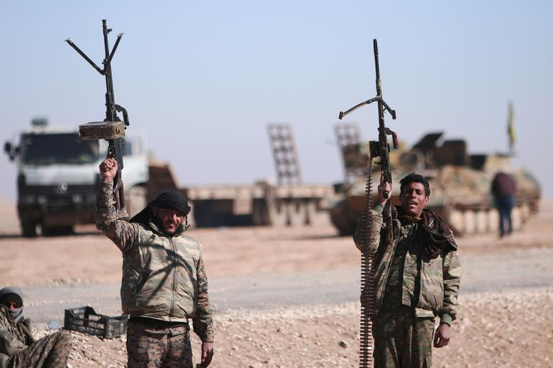 Syrian Democratic Forces (SDF) fighters hold up their weapons in the north of Raqqa city, Syria February 3, 2017. Picture taken February 3, 2017. REUTERS/Rodi Said/File Photo