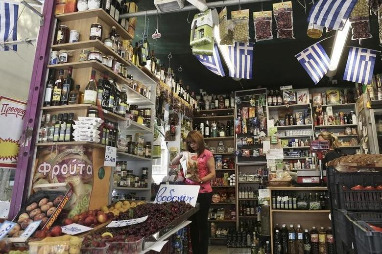 A woman buys products in a grocery market in Athens July 2, 2013. REUTERS/John Kolesidis