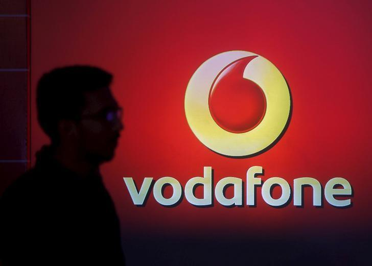 A man casts silhouette onto an electronic screen displaying logo of Vodafone India after a news conference to announce the half year results in Mumbai, November 10, 2015. REUTERS/Shailesh Andrade/Files