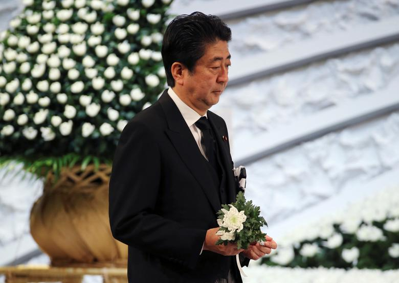 Japanese Prime Minister Shinzo Abe holds a chrysanthemum to offer for the victims of the March 11, 2011 earthquake and tsunami during the national memorial service in Tokyo, Saturday, March 11, 2017.  REUTERS/Koji Sasahara/Pool