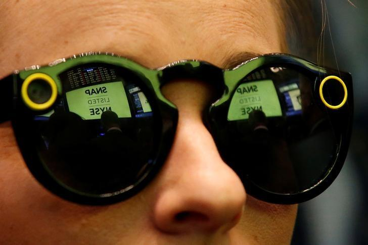 A woman wears Snapchat Spectacles on the floor of the New York Stock Exchange (NYSE) while waiting for Snap Inc. to list their IPO in New York, U.S., March 2, 2017. REUTERS/Brendan McDermid