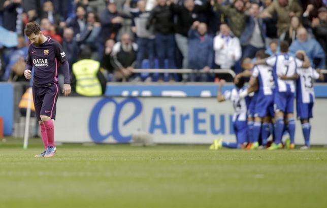 3月12日、サッカーのスペイン1部、首位バルセロナは敵地でデポルティボに1─2で敗れ、昨年10月以来のリーグ戦黒星で2位に後退した。写真左は2失点目にうなだれるバルセロナのリオネル・メッシ(2017年 ロイター/Miguel Vidal)
