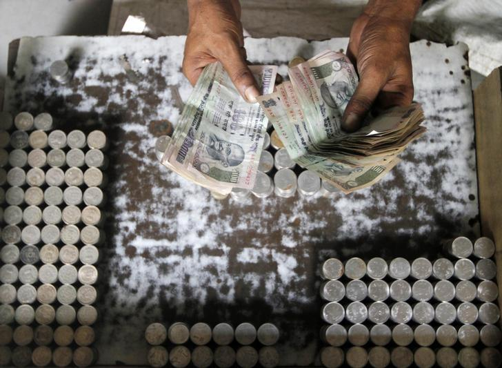 A man exchanging currency counts 100 rupee notes along a roadside in Kolkata August 30, 2013.  REUTERS/Rupak De Chowdhuri/Files