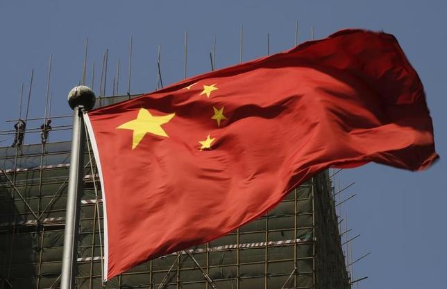 3月10日、新興国市場はまもなく、デフレというよりも世界的なインフレの発信地となるかもしれない。写真は、中国の国旗と建設現場で働く作業員。北京で2013年4月撮影(2017年 ロイター/Kim Kyung-Hoon)