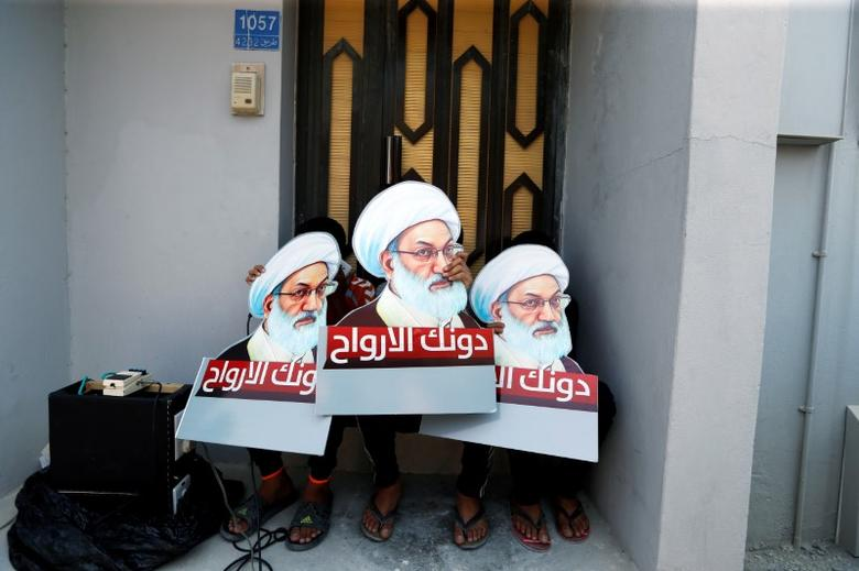 Protesters holding placards with images of Bahrain's leading Shi'ite cleric Isa Qassim, shout religious slogans during an anti-government protest after Friday prayers in the village of Diraz, west of Manama, Bahrain August 12, 2016.  REUTERS/Hamad I Mohammed