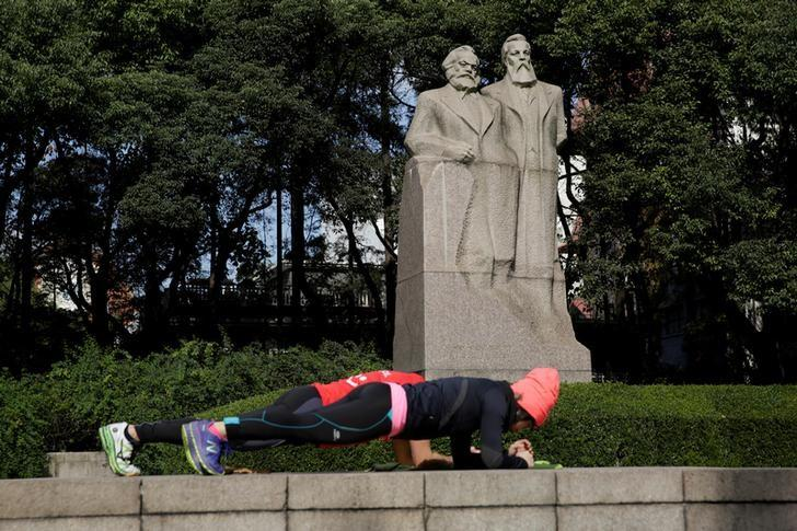 A couple exercises in front of the statue of German philosophers Karl Marx and Friedrich Engels at a park in Shanghai, China December 2, 2016. REUTERS/Aly Song/Files