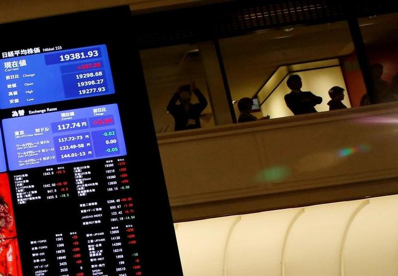 People are seen behind an electronic board showing stock prices after the New Year opening ceremony at the Tokyo Stock Exchange (TSE), in Tokyo, Japan, January 4, 2017.  REUTERS/Kim Kyung-Hoon