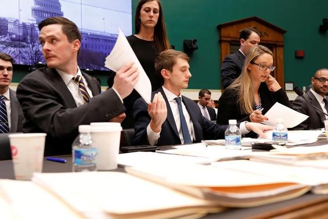 3月14日、スパイサー米大統領報道官と共和党議会指導部は、オバマ前政権による医療保険制度改革(オバマケア)改廃法案について修正を検討していることを明らかにした。写真はワシントン・米議会議事堂で行われた米国下院エネルギーおよび商業対策委員会による公聴会で、オバマケア改革案を手渡すスタップら(2017年 ロイター/Aaron P. Bernstein)