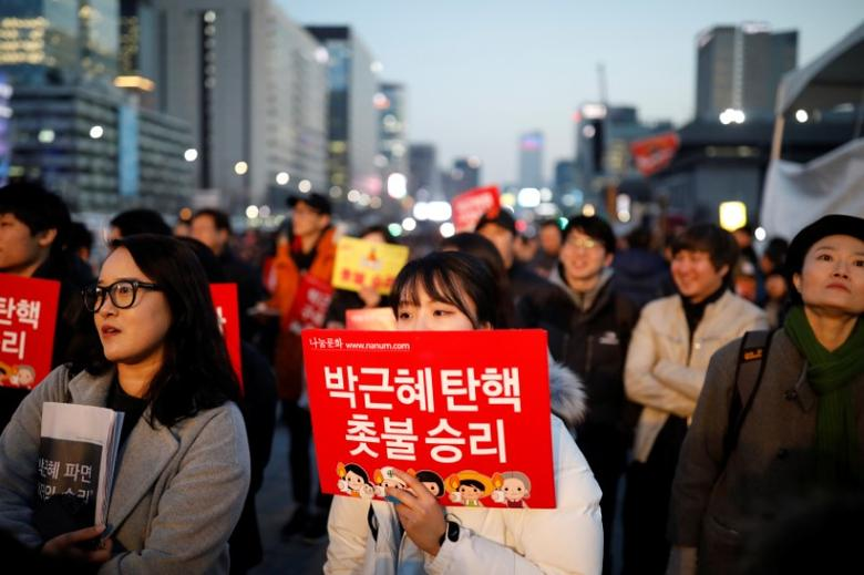 People attend a rally calling for impeached President Park Geun-hye's arrest in central Seoul, South Korea, March 10, 2017. The sign reads ''Park Geun-hye is impeached, We won''.   REUTERS/Kim Hong-Ji