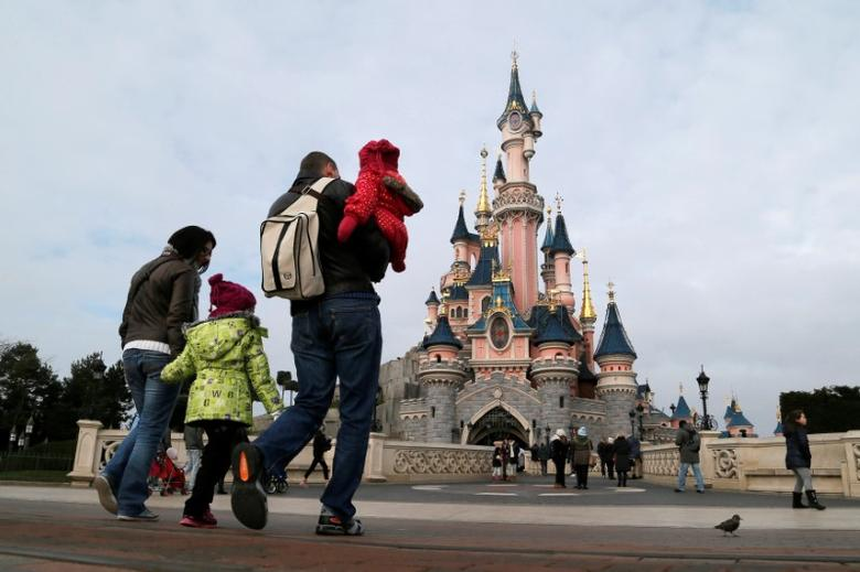 FILE PHOTO: Visitors walk towards the Sleeping Beauty Castle during a visit to the Disneyland Paris, France, January 21, 2015.   REUTERS/Gonzalo Fuentes/File Photo - RTX30GBA