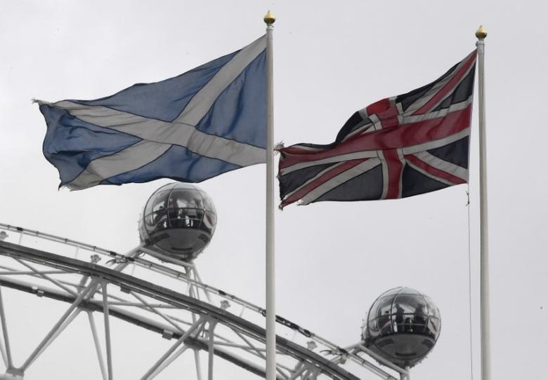 The British Union Flag (R) and a Scottish Saltire flag fly above the Scottish Office in Whitehall, with the London Eye wheel seen behind, in London, Britain, March 14, 2017. REUTERS/Toby Melville