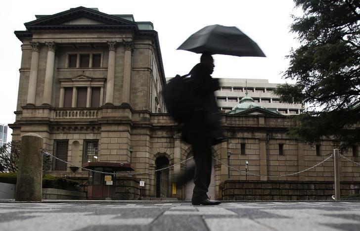 2013年12月,东京,一名打伞的行人路过日本央行大楼。REUTERS/Yuya Shino