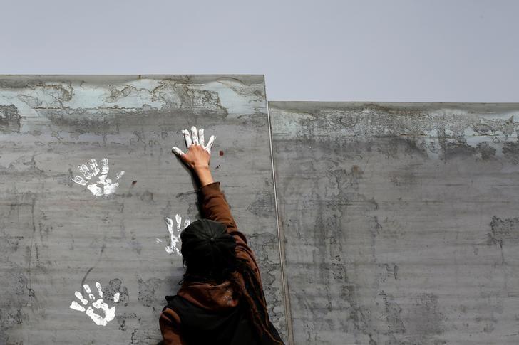 An activist paints the U.S.-Mexico border wall between Ciudad Juarez and New Mexico as a symbol of protest against U.S. President Donald Trump's new immigration reform in Ciudad Juarez, Mexico February 26, 2017. REUTERS/Jose Luis Gonzalez/Files