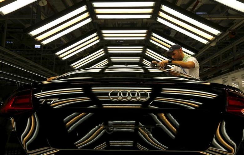 A worker stands next to a car on the assembly line as serial production of the new Audi TT roadster starts at the Audi plant in Gyor, west of Budapest November 5, 2014.  REUTERS/Laszlo Balogh/File Photo