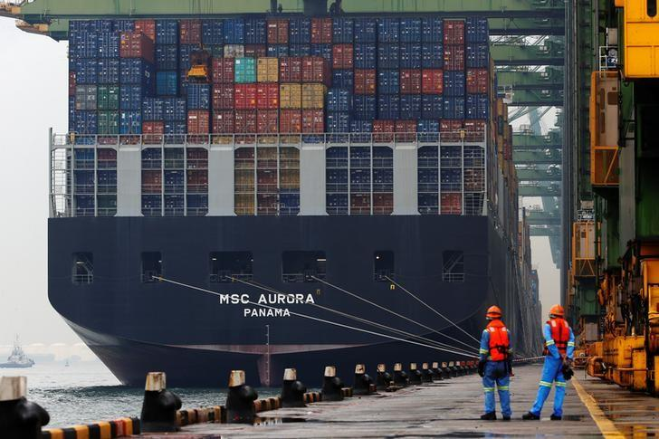 Workers look as a container ship is unloaded at a berth in a PSA International port terminal in Singapore September 25, 2013.  REUTERS/Edgar Su/Files