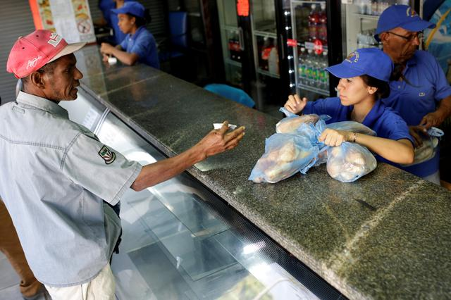 A man buys bread at a bakery in Caracas, Venezuela March 17, 2017. REUTERS/Marco Bello