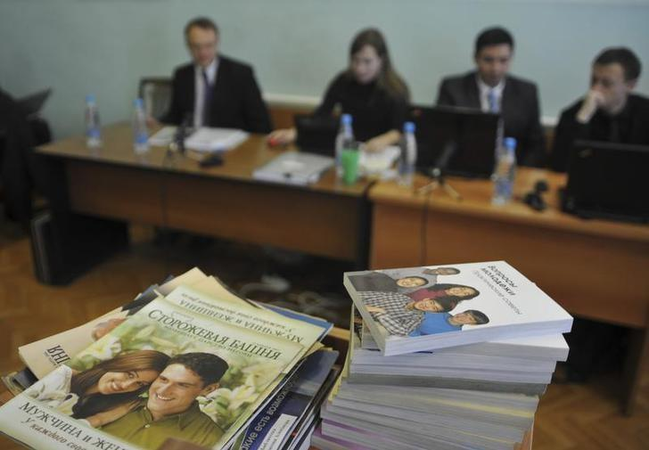 Stacks of booklets distributed by Alexander Kalistratov (L), the local leader of a Jehovah's Witnesses congregation, are seen during the court session in the Siberian town of Gorno-Altaysk, December 16, 2010. REUTERS/Alexandr Tyryshkin/Files