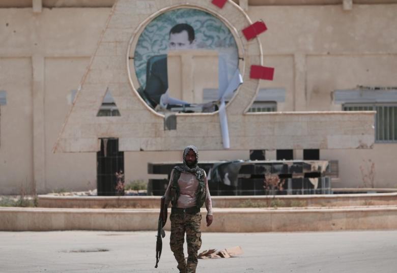A Kurdish fighter from the People's Protection Units (YPG) carries his weapon as he walks at the faculty of economics where a defaced picture of Syrian President Bashar al-Assad is seen in the background, in the Ghwairan neighborhood of Hasaka, Syria, August 22, 2016. REUTERS/Rodi Said