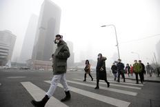 A pesar de que el primer ministro chino, Li Keqiang, se comprometió a garantizar que los cielos azules nunca se convertirán en un lujo en el país, una empresa respaldada por el Estado está haciendo un rápido negocio vendiendo latas con aire fresco de un bosque del oeste de China. En la imagen de archivo, un hombre lleva una máscara frente a un edificio de oficinas durante una alerta roja de contaminación en el distrito de negocios de Pekín, China, el 21 de diciembre de 2016. REUTERS/Jason Lee