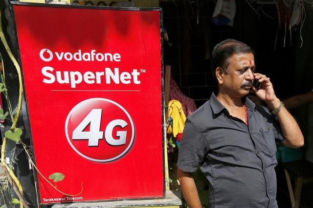 A man speaks on his mobile phone next to a Vodafone advertisement in Kolkata, India, September 26, 2016. REUTERS/Rupak De Chowdhuri