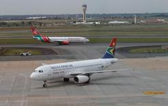 A South African Airways aircraft (bottom) arrives as a Kenya Airways aircraft prepares to take off at the OR Tambo International Airport in Johannesburg, South Africa, March 8, 2017. REUTERS/Siphiwe Sibeko