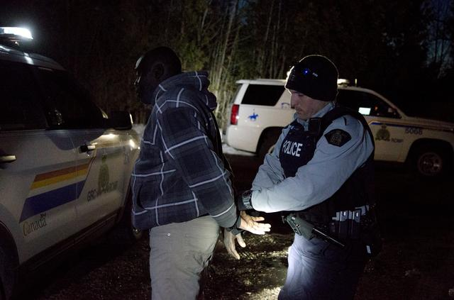 A man who claimed to be from Sudan who kept saying ''I just want to be safe'' is handcuffed by a Royal Canadian Mounted Police (RCMP) officer after he illegally crossed the U.S.-Canada border leading into Hemmingford, Quebec, Canada, March 20, 2017. REUTERS/Christinne Muschi