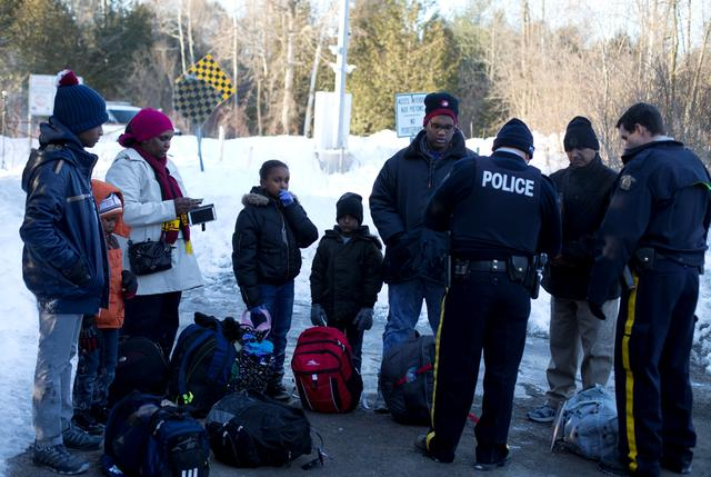 A family who claimed to be from Sudan are met by Royal Canadian Mounted Police (RCMP) officers as they illegally cross the U.S.-Canada border leading into Hemmingford, Quebec, Canada, March 20, 2017. REUTERS/Christinne Muschi