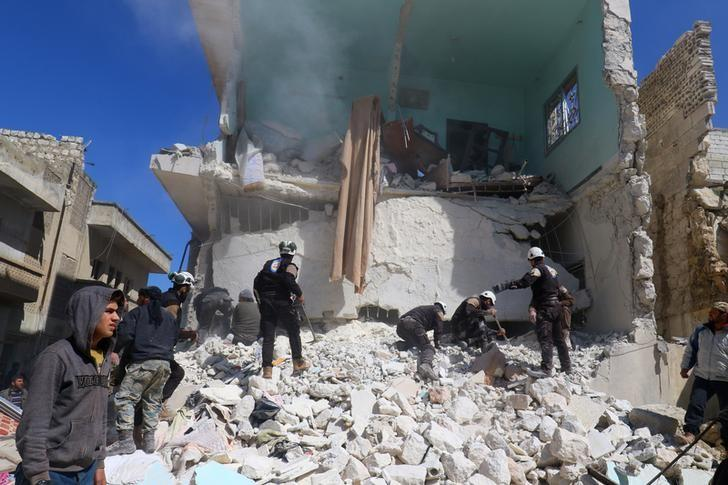 People and civil defence personnel remove rubble as they look for survivors at a damaged site after an air strike on rebel-held Idlib city, Syria March 19, 2017. REUTERS/Ammar Abdullah