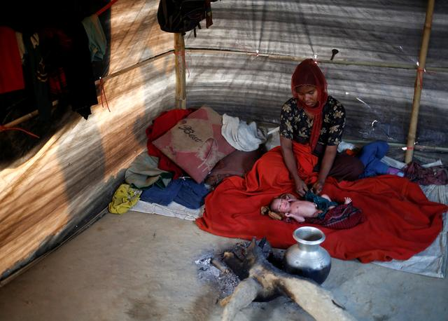 Rehana Begum, 25, sits near her one-day-old unnamed daughter inside their shelter at Kutupalang unregistered refugee camp in Cox's Bazar, Bangladesh, February 10, 2017. REUTERS/Mohammad Ponir Hossain
