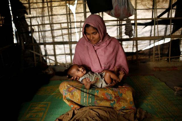 Jamalida, 30, holds her two-month-old daughter Shahida as she poses for a photograph inside their shelter in Kutupalang unregistered refugee camp in Cox's Bazar, Bangladesh, February 10, 2017. REUTERS/Mohammad Ponir Hossain